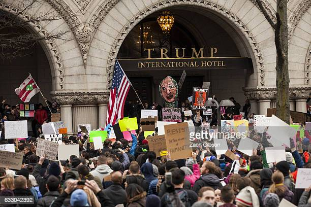 Demonstrators gather outside of the Trump Hotel International during a protest on January 29 2017 in Washington DC Protestors in Washington and...