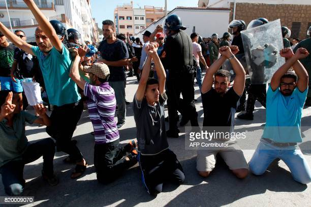 Demonstrators gesture calling for the release of imprisoned members of the alHirak alShaabi movement in front of Moroccan security forces during a...
