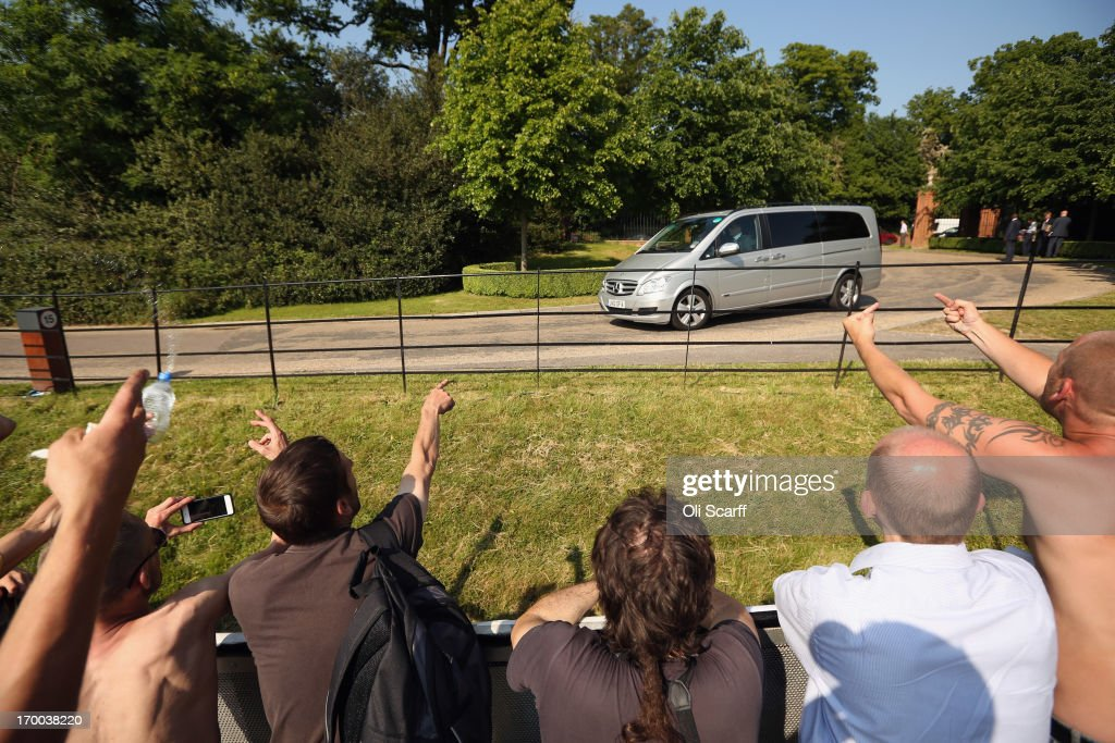 Demonstrators gesture from the protester encampment as vehicles arrive at The Grove hotel, which is hosting the annual Bilderberg conference on June 6, 2013 in Watford, England. The traditionally secretive conference, which has taken place since 1954, is expected to be attended by politicians, bank bosses, billionaires, chief executives and European royalty.