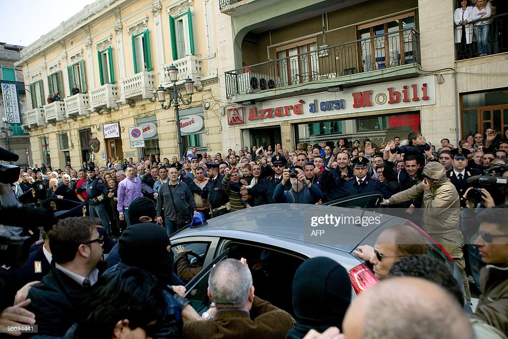 Demonstrators heckle police as Giovanni Tegano a top mafia boss is escorted from police headquarters after his arrest in southern Italy city of...