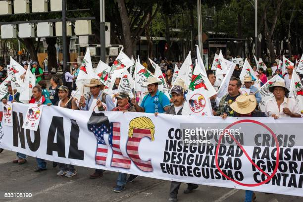 Demonstrators hold a banner and flags during a protest against the North American Free Trade Agreement in Mexico City Mexico on Wednesday Aug 16 2017...