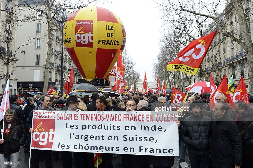 Demonstrators hold a banner reading 'Angry workers of Temenos-Viveo France. Products in India, money in Switzerland, unemployed in France', as they take part in a protest led by the CGT union as part of a day of interprofessional protest against precariousness, flexibility, unemployment and low wages on January 10, 2013 in front of the French employers' federation MEDEF headquarters in Paris.