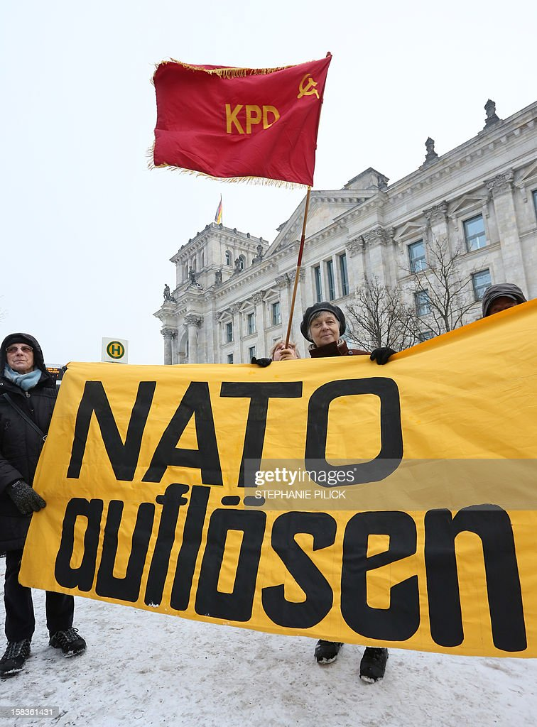 Demonstrators hold a banner reading 'Dissolve NATO' to protest against the deployment of Patriot missiles and soldiers on Turkey's volatile border with war-ravaged Syria on December 14, 2012 in front of the Reichstag building housing the Bundestag (lower house of parliament) in Berlin. The German parliament approved by a wide majority the deployment of Patriot missiles to help Turkey defend its border against conflict-riven Syria as part of a NATO mission. AFP PHOTO / STEPHANIE PILICK GERMANY OUT