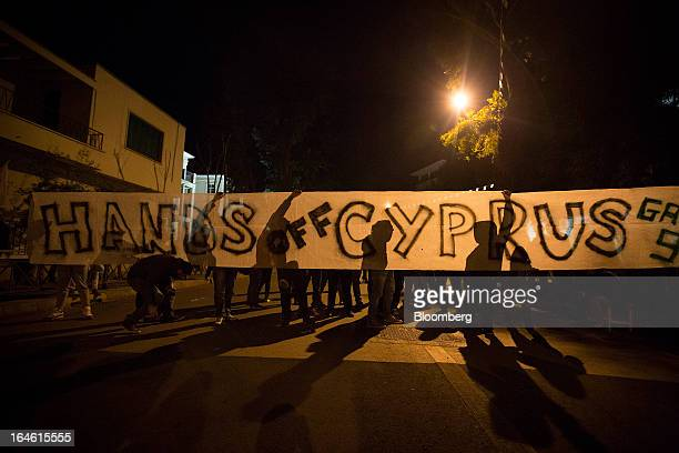 Demonstrators hold a banner reading 'Hands off Cyprus' during a protest outside the European Union House in Nicosia Cyprus on Sunday March 24 2013...