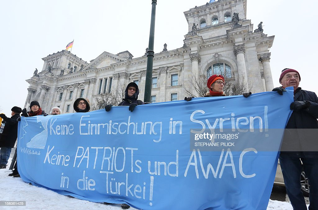Demonstrators hold a banner reading 'No interfering in matters of Syria! No patriots and AWAC in Turkey!' to protest against the deployment of Patriot missiles and soldiers on Turkey's volatile border with war-ravaged Syria on December 14, 2012 in front of the Reichstag building housing the Bundestag (lower house of parliament) in Berlin. The German parliament approved by a wide majority the deployment of Patriot missiles to help Turkey defend its border against conflict-riven Syria as part of a NATO mission.