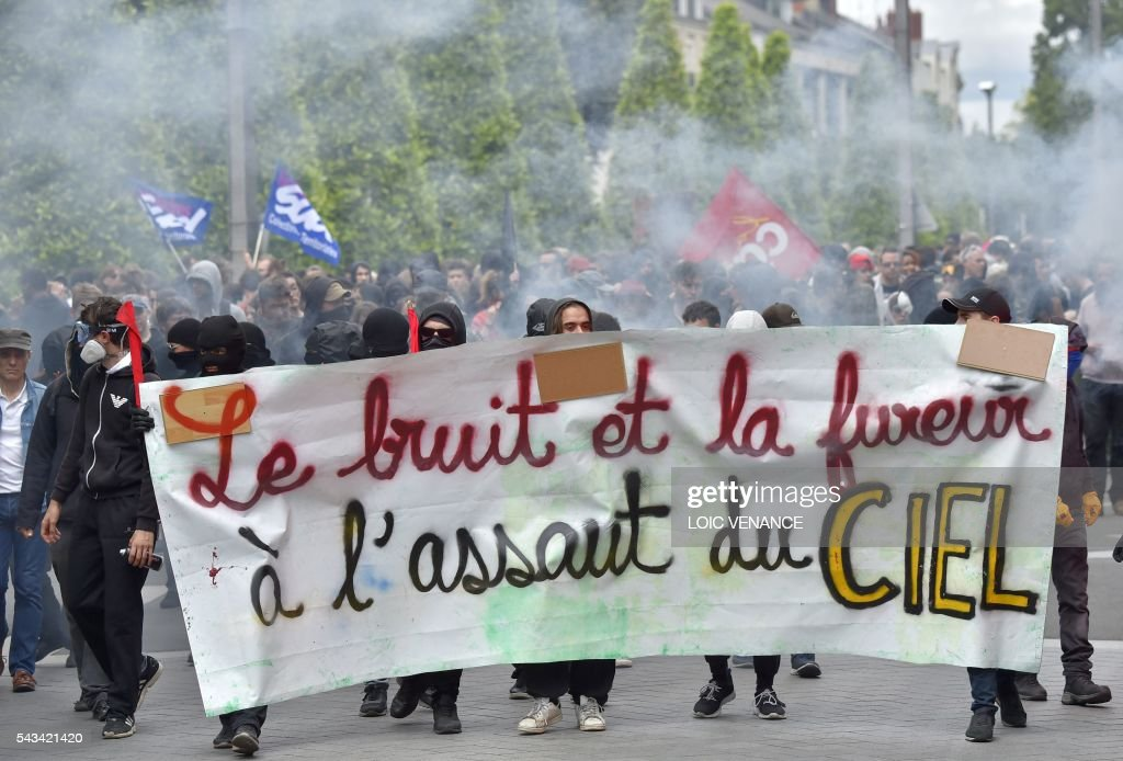 Demonstrators hold a banner reading 'noise and fury to conquer the sky' during a protest against controversial labour reforms, on June 28, 2016 in Nantes, western France. People took to the streets in France on June 28 in the latest protest march in a marathon campaign against the French Socialist government's job market reforms. Last month the government used a constitutional manoeuvre to push the bill through the lower house without a vote in the face of opposition from Socialist backbenchers. / AFP / LOIC