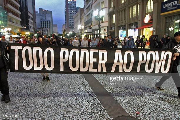 Demonstrators hold a banner reading 'Power to the people' during a protest against the FIFA's decision of keeping Curitiba as venue of the 2014...