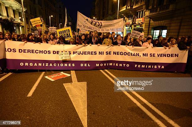 Demonstrators hold a banner reading 'Womens rights are not for negotiation nor for sale' during a demonstration against the Spanish government's...