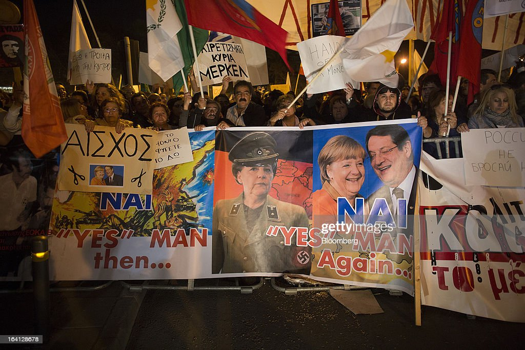 Demonstrators hold a banner showing photographs of Germany's Chancellor Angela Merkel, center, and Cyprus's President Nicos Anastasiades during a protest outside the parliament against bank deposit tax plans in Nicosia, Cyprus, on Tuesday, March 19, 2013. Euro-area finance ministers told Cyprus to raise 5.8 billion euros ($7.5 billion) from bank depositors to unlock emergency loans, maintaining the revenue target while suggesting sparing small-scale savers. Photographer: Simon Dawson/Bloomberg via Getty Images