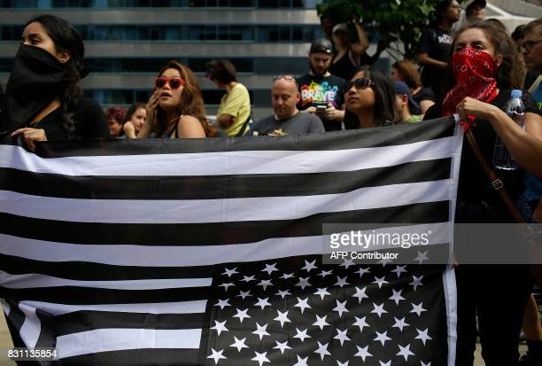 Demonstrators hold a black American flag upside they as they protest against hate white supremacy groups and President Donald Trump on Sunday August...