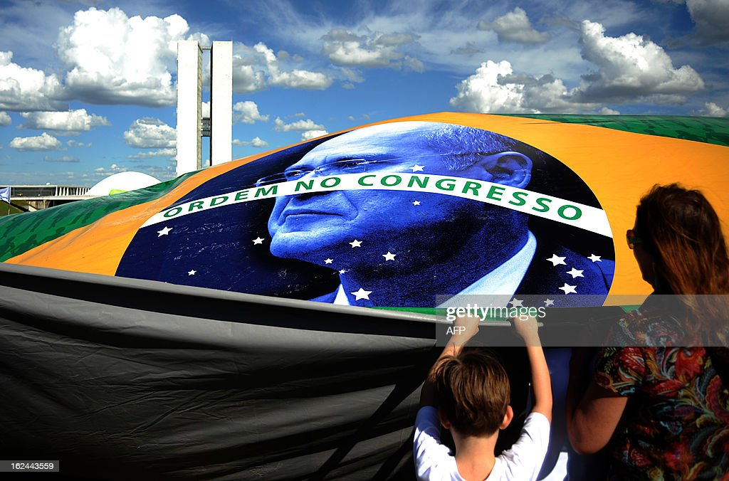 Demonstrators hold a Brazilian flag with the picture of the president of the Brazilian Senate, Renan Calheiros reading 'Order in Congress' during a protest against him, in front of the Brazilian National Congress, in Brasilia, on February 23, 2013. Calheiros was elected by his colleagues despite many corruption claims over him. An undersigned made on the internet with over then 1,5 million signatures was delivered by activists to the Senate this week, demanding his impeachment. AFP PHOTO/PEDRO LADEIRA