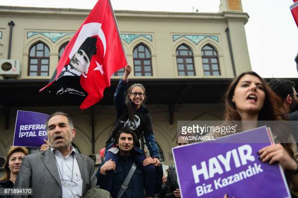 Demonstrators hold a flag of Mustafa Kemal Ataturk founder of modern Turkey and a placard reading 'No This is just the beginning' during a protest at...