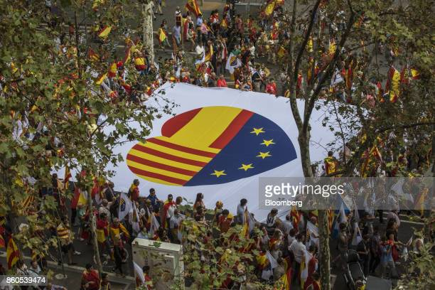 Demonstrators hold a giant banner with a Spanish National flag a Catalan flag also known as the Senyera and the stars of the European Union flag in a...