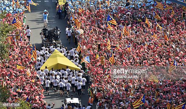 Demonstrators hold a giant yellow cursor as they gather on Meridiana street as they wave 'Estelada' flags during celebrations of Catalonia's National...