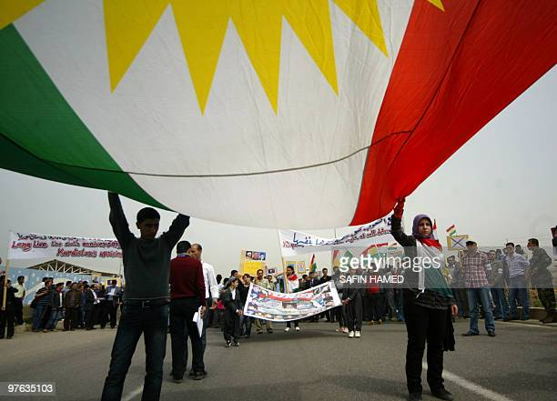 Demonstrators hold a large Kurdish flag in Arbil northern Iraq on March 11 on the anniversary of the 2004 clashes between Kurds and Syrian security...