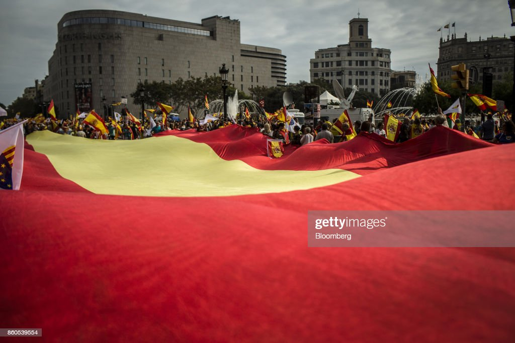 Demonstrators hold a massive Spanish national flag as they gather on Catalonia Square in support of Spanish unity during a march on Spain's National Day in Barcelona, Spain, on Thursday, Oct. 12, 2017. Prime MinisterMariano Rajoygave his Catalan antagonist Carles Puigdemont five days to clarify whether he has declared independence from Spain or not as the country prepared for its national holiday on Thursday. Photographer: Angel Garcia/Bloomberg via Getty Images