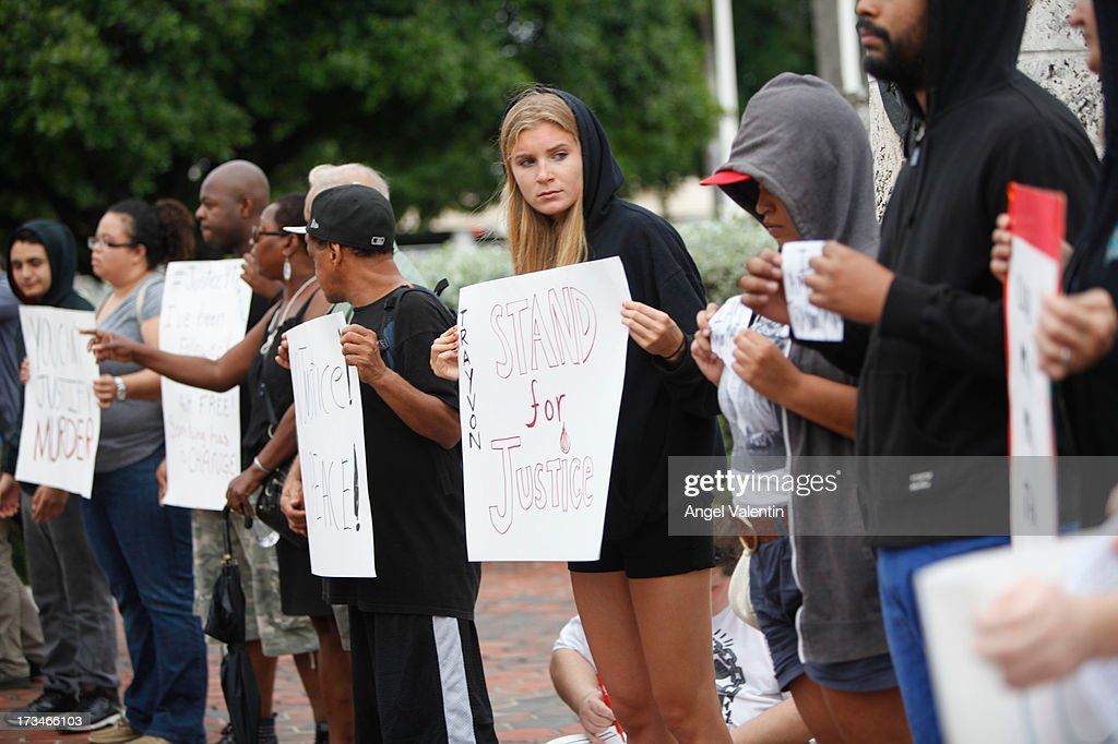 Demonstrators hold a peaceful rally at the Torch of Freedom in downtown Miami a day after the verdict to the George Zimmerman murder trail on July 14, 2013 in Miami, Florida. A jury found neighborhood watch volunteer, George Zimmerman not guilty of shooting and killing 17-year-old Trayvon Martin after an altercation in February 2012.