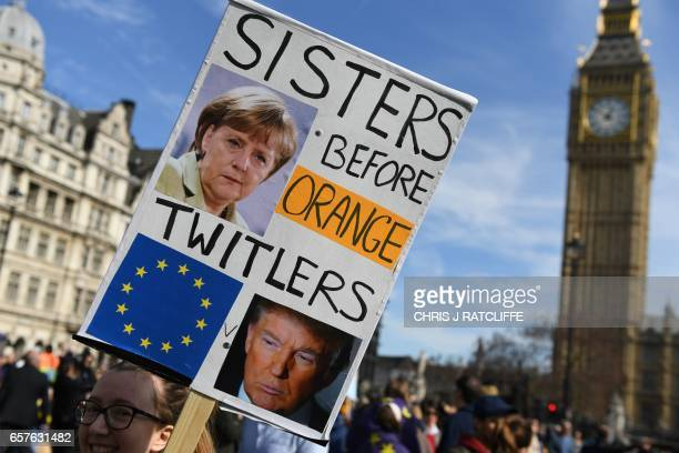 Demonstrators hold a placard depicting Germany's Chancellor Angela Merkel and US President Donald Trump as they pass the Houses of Parliament during...