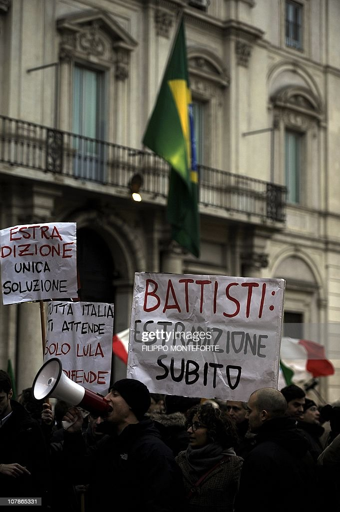 Demonstrators hold a placard reading 'Battisti, extradition now' in front of Brazil's embassy to protest Brazilian President Lula's refusal to extradite ex-militant Cesare Battisti on January 4, 2011 at Piazza Navona in Rome. President Luiz Inacio Lula da Silva's refusal on December 31 to extradite Battisti, a member of the Armed Proletariat for Communism (PAC), a radical and armed left-wing group that killed several people in the 1970s, sparked a wave of indignation across Italy. Battisti has been found guilty of the group's 1978-1979 murders of a prison guard, a special investigator of terrorist organisations, a butcher and a jeweller, and in 1993 was sentenced in his absence to life in prison.