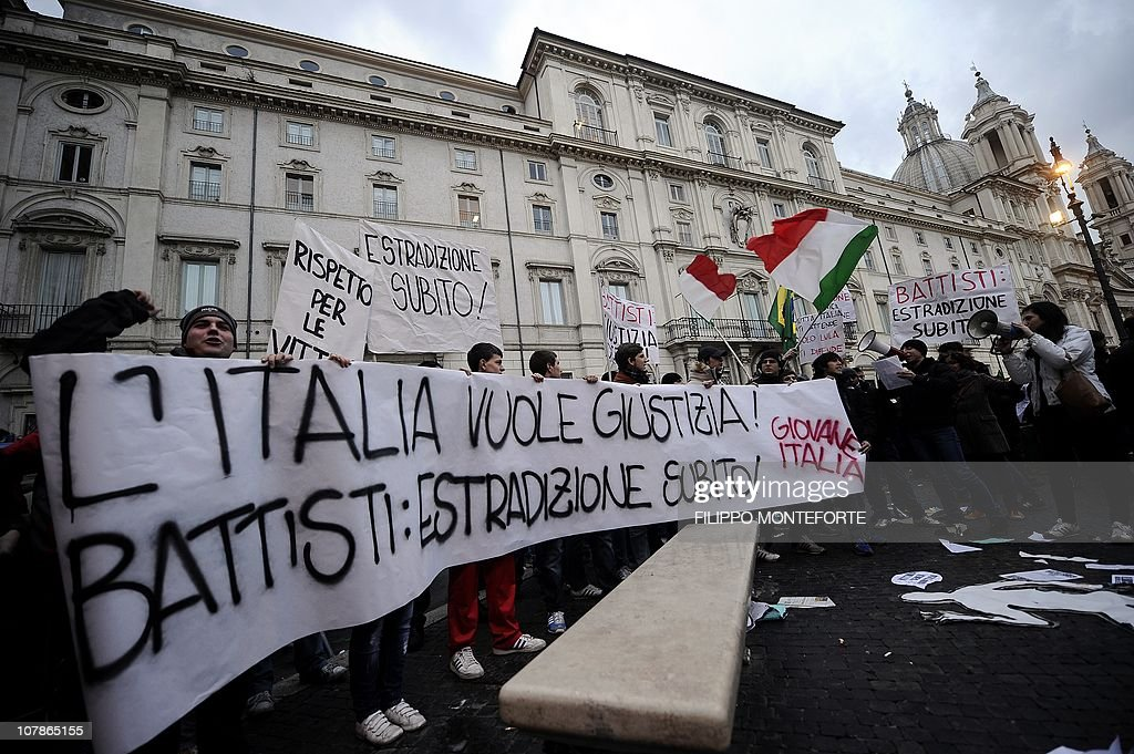 Demonstrators hold a placard reading 'Italy wants justice. Battisti, extradition now' in front of Brazil's embassy (L) to protest Brazilian President Lula's refusal to extradite ex-militant Cesare Battisti on January 4, 2011 at Piazza Navona in Rome. President Luiz Inacio Lula da Silva's refusal on December 31 to extradite Battisti, a member of the Armed Proletariat for Communism (PAC), a radical and armed left-wing group that killed several people in the 1970s, sparked a wave of indignation across Italy. Battisti has been found guilty of the group's 1978-1979 murders of a prison guard, a special investigator of terrorist organisations, a butcher and a jeweller, and in 1993 was sentenced in his absence to life in prison.