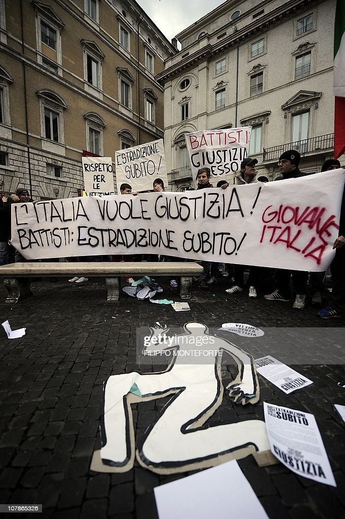 Demonstrators hold a placard reading 'Italy wants justice. Battisti, extradition now' in front of Brazil's embassy to protest Brazilian President Lula's refusal to extradite ex-militant Cesare Battisti on January 4, 2011 at Piazza Navona in Rome. President Luiz Inacio Lula da Silva's refusal on December 31 to extradite Battisti, a member of the Armed Proletariat for Communism (PAC), a radical and armed left-wing group that killed several people in the 1970s, sparked a wave of indignation across Italy. Battisti has been found guilty of the group's 1978-1979 murders of a prison guard, a special investigator of terrorist organisations, a butcher and a jeweller, and in 1993 was sentenced in his absence to life in prison. AFP PHOTO / FILIPPO MONTEFORTE
