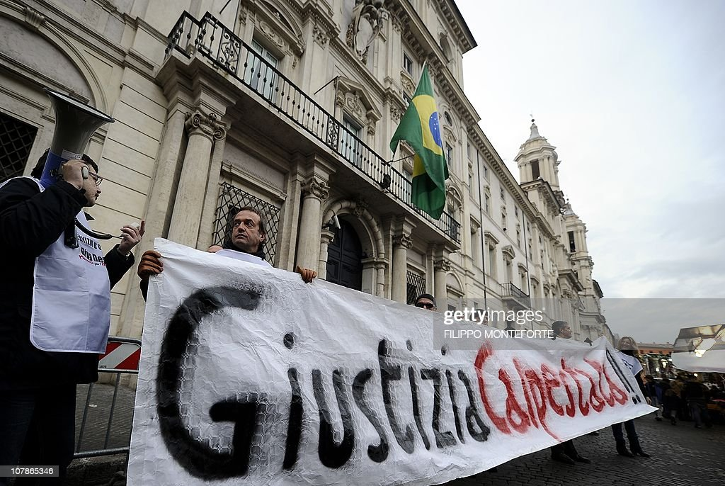Demonstrators hold a placard reading 'Justice trampled' in front of Brazil's embassy to protest Brazilian President Lula's refusal to extradite ex-militant Cesare Battisti on January 4, 2011 at Piazza Navona in Rome. President Luiz Inacio Lula da Silva's refusal on December 31 to extradite Battisti, a member of the Armed Proletariat for Communism (PAC), a radical and armed left-wing group that killed several people in the 1970s, sparked a wave of indignation across Italy. Battisti has been found guilty of the group's 1978-1979 murders of a prison guard, a special investigator of terrorist organisations, a butcher and a jeweller, and in 1993 was sentenced in his absence to life in prison. AFP PHOTO / FILIPPO MONTEFORTE
