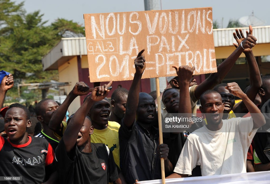 Demonstrators hold a placard reading 'We want peace 2013 = Petrol' and shout slogans at the airport in Bangui, as the President of the Central African Republic greets the current president of the African Union and President of Benin, on December 30, 2012. Rebels in the Central African Republic who have advanced towards the capital Bangui warned they could enter the city even as the head of the African Union prepared to launch peace negotiations. Central African President Francois Bozize also stated today he was open to a national unity government after talks with rebel leaders and that he would not run for president in 2016. AFP PHOTO/ SIA KAMBOU