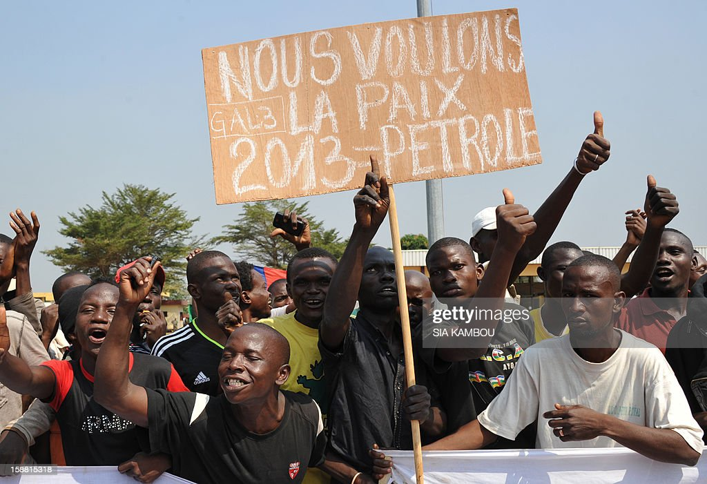 Demonstrators hold a placard reading 'We want peace 2013 = Petrol' at the airport in Bangui, as the President of the Central African Republic greets the current president of the African Union and President of Benin, on December 30, 2012. Rebels in the Central African Republic who have advanced towards the capital Bangui warned they could enter the city even as the head of the African Union prepared to launch peace negotiations. Central African President Francois Bozize also stated today he was open to a national unity government after talks with rebel leaders and that he would not run for president in 2016.