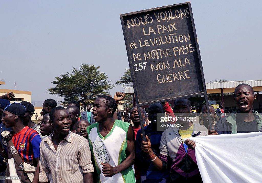 Demonstrators hold a placard reading 'We want peace and the development of our country, we refuse war' at the airport in Bangui, as the President of the Central African Republic greets the current president of the African Union and President of Benin, on December 30, 2012. Rebels in the Central African Republic who have advanced towards the capital Bangui warned they could enter the city even as the head of the African Union prepared to launch peace negotiations. Central African President Francois Bozize also stated today he was open to a national unity government after talks with rebel leaders and that he would not run for president in 2016. AFP PHOTO/ SIA KAMBOU