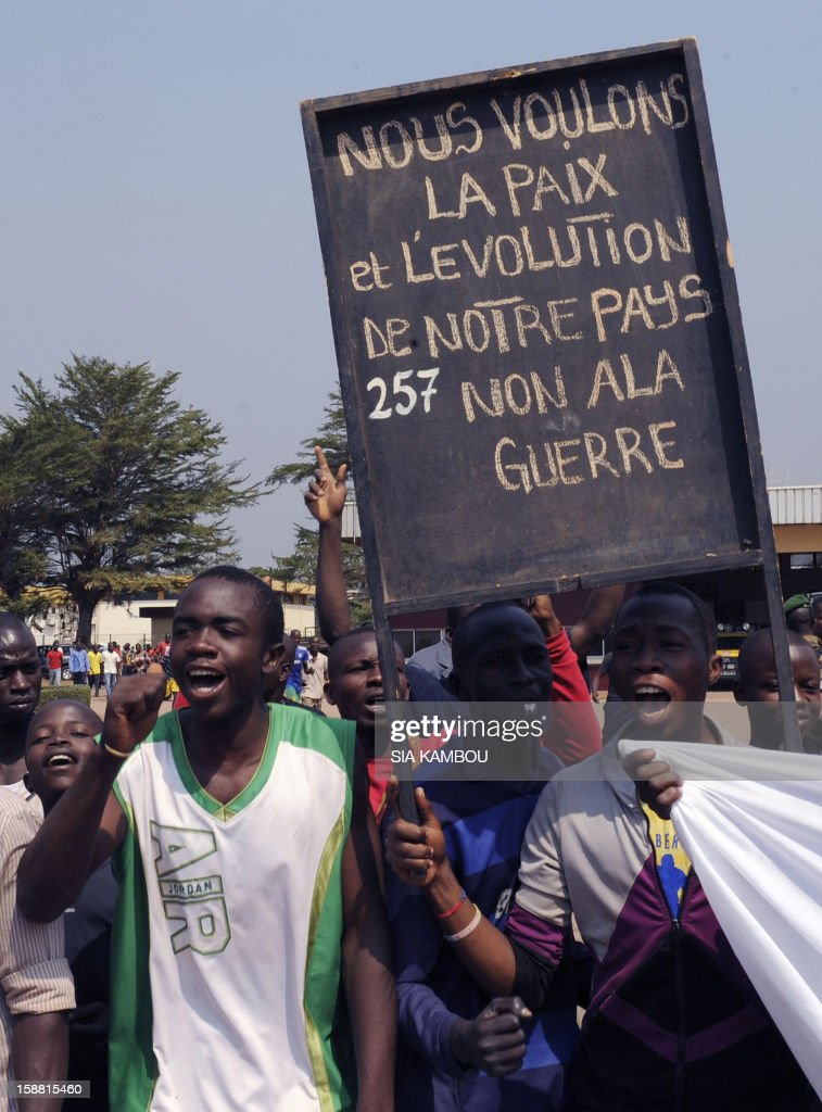 Demonstrators hold a placard reading 'We want peace and the development of our country, we refuse war' at the airport in Bangui, as the President of the Central African Republic greets the current president of the African Union and President of Benin, on December 30, 2012. Rebels in the Central African Republic who have advanced towards the capital Bangui warned they could enter the city even as the head of the African Union prepared to launch peace negotiations. Central African President Francois Bozize also stated today he was open to a national unity government after talks with rebel leaders and that he would not run for president in 2016.