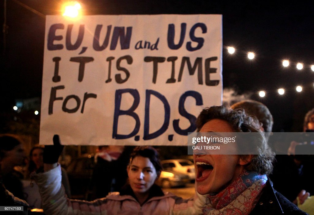 Demonstrators hold a placard urging the international community to take action against Israel's settlement policy in the occupied territories as...