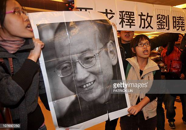 Demonstrators hold a portrait of China's detained Nobel Peace Prize winner Liu Xiaobo demanding his immediate release during a protest in the lobby...