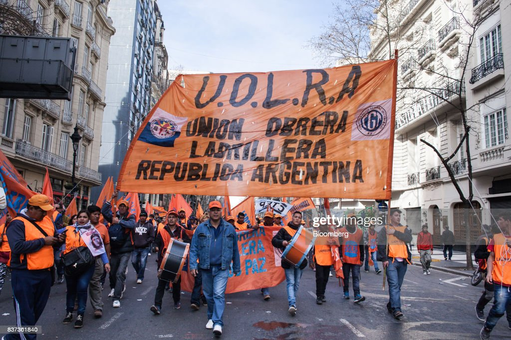 Demonstrators hold a sign and flags during a protest in Buenos Aires, Argentina, on Tuesday, Aug. 22, 2017. Union groups protested Argentinean President Mauricio Marcri's economic policies. Photographer: Erica Canepa/Bloomberg via Getty Images