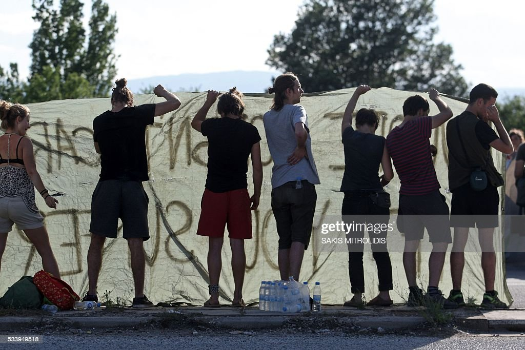 Demonstrators hold a sign during the forced evacuation of migrants and refugees from a makeshift camp close to the Greece-Macedonia border, near the village of Idomeni on May 24, 2016. Greek police on May 24 moved hundreds of migrants out of the overcrowded camp of Idomeni, launching a major operation to clear up the squalid tent city where thousands fleeing war and poverty had lived for months. In an operation that began shortly after sunrise, Greek police said they had put more than 1,500 people on buses to newly opened camps near Greece's second city Thessaloniki, about 80 kilometres (50 miles) to the south. MITROLIDIS