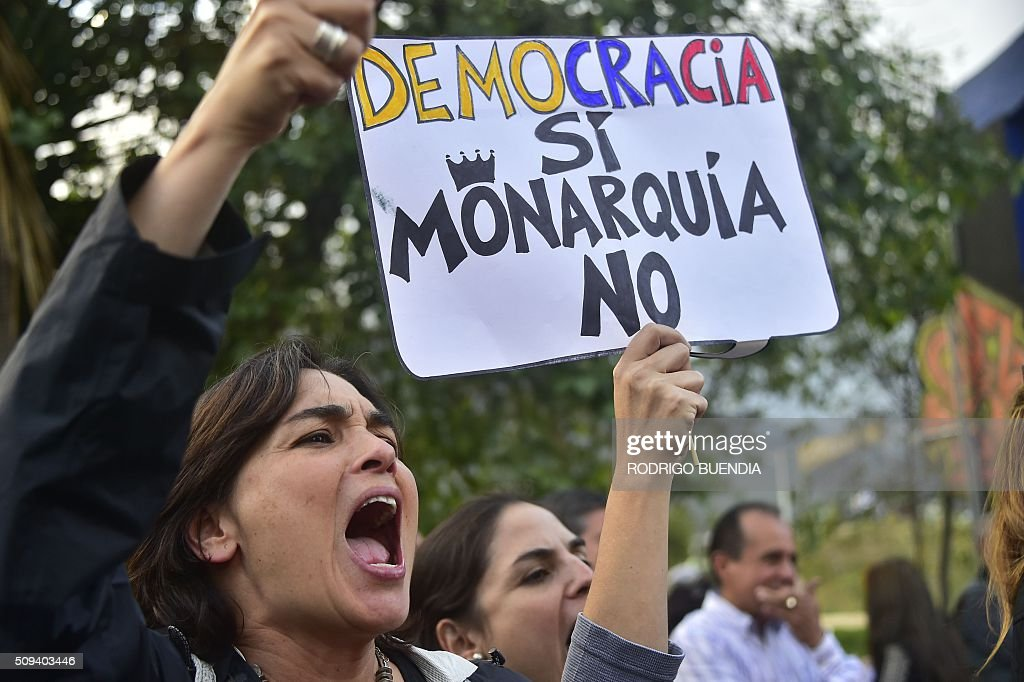 Demonstrators hold a sign reading 'Democracy yes, Monarchy not' as they protest against the government of Ecuadorean President Rafael Correa in Quito on February 10, 2016. AFP PHOTO / RODRIGO BUENDIA / AFP / RODRIGO BUENDIA
