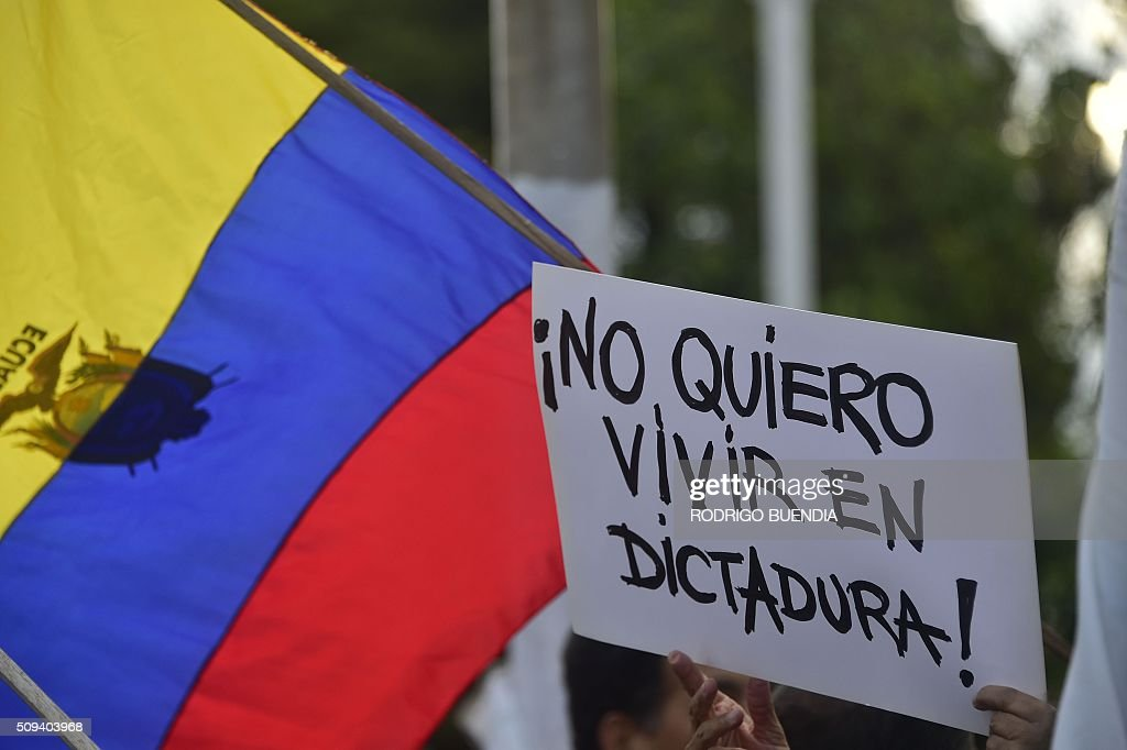 Demonstrators hold a sign reading 'I don't want to live in a dictatorship!' as they protest against the government of Ecuadorean President Rafael Correa in Quito on February 10, 2016. AFP PHOTO / RODRIGO BUENDIA / AFP / RODRIGO BUENDIA