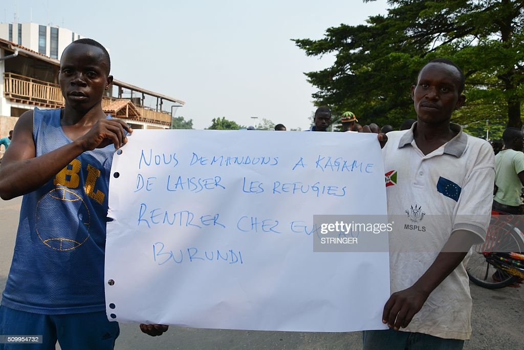 Demonstrators hold a sign reading 'we ask Kagame to let the refugees come back home to Burundi' on February 13, 2016 in Bujumbura in front of the Rwandan embassy during a protest against Rwanda. Rwanda is to relocate refugees from Burundi to other countries, amid accusations Kigali was meddling in the affairs of its troubled neighbour. UN experts told the Security Council that Rwanda has recruited and trained refugees from Burundi, among them children, who wanted to remove Burundi's President Pierre Nkurunziza from power. Burundi has repeatedly accused Rwanda of backing rebels intent on overthrowing the government in Bujumbura. Kigali has fiercely denied the accusations. Burundi has been in turmoil since Nkurunziza announced plans in April to run for a third term, which he went on to win. Hundreds of people have been killed and at least 230,000 have fled the country. Some 75,000 Burundian refugees are in Rwanda, according to the UN refugee agency, UNHCR. / AFP / STRINGER