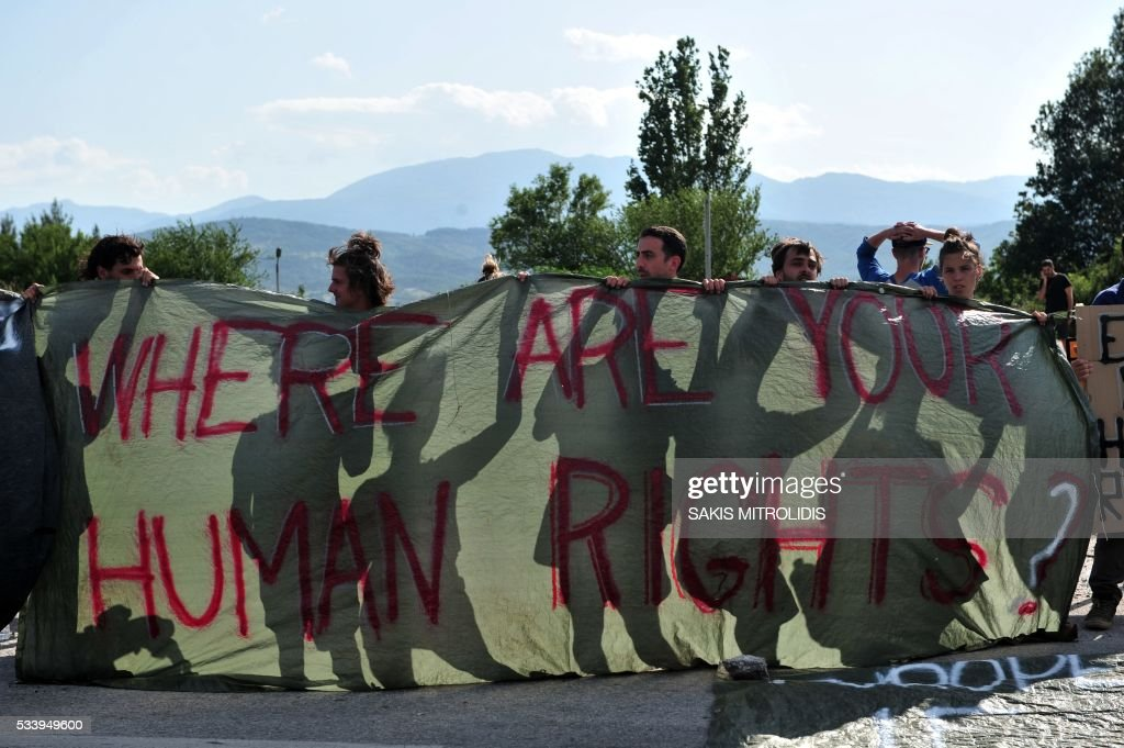 Demonstrators hold a sign reading 'Where are your human rights?' during the forced evacuation of migrants and refugees from a makeshift camp close to the Greece-Macedonia border, near the village of Idomeni on May 24, 2016. Greek police on May 24 moved hundreds of migrants out of the overcrowded camp of Idomeni, launching a major operation to clear up the squalid tent city where thousands fleeing war and poverty had lived for months. In an operation that began shortly after sunrise, Greek police said they had put more than 1,500 people on buses to newly opened camps near Greece's second city Thessaloniki, about 80 kilometres (50 miles) to the south. MITROLIDIS
