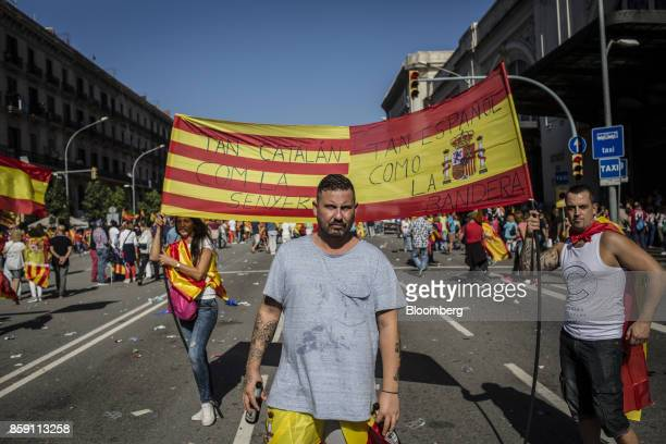 Demonstrators hold a Spanish national flag and a Catalan flag also known as the Senyera during a protest for Spanish unity on the Marqus de la...