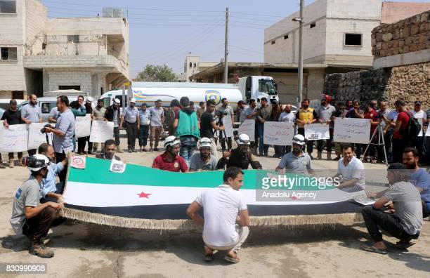 Demonstrators hold a Syrian flag and placards as they take part in a protest for 7 members of Syrian civil defense organization White Helmets shot...