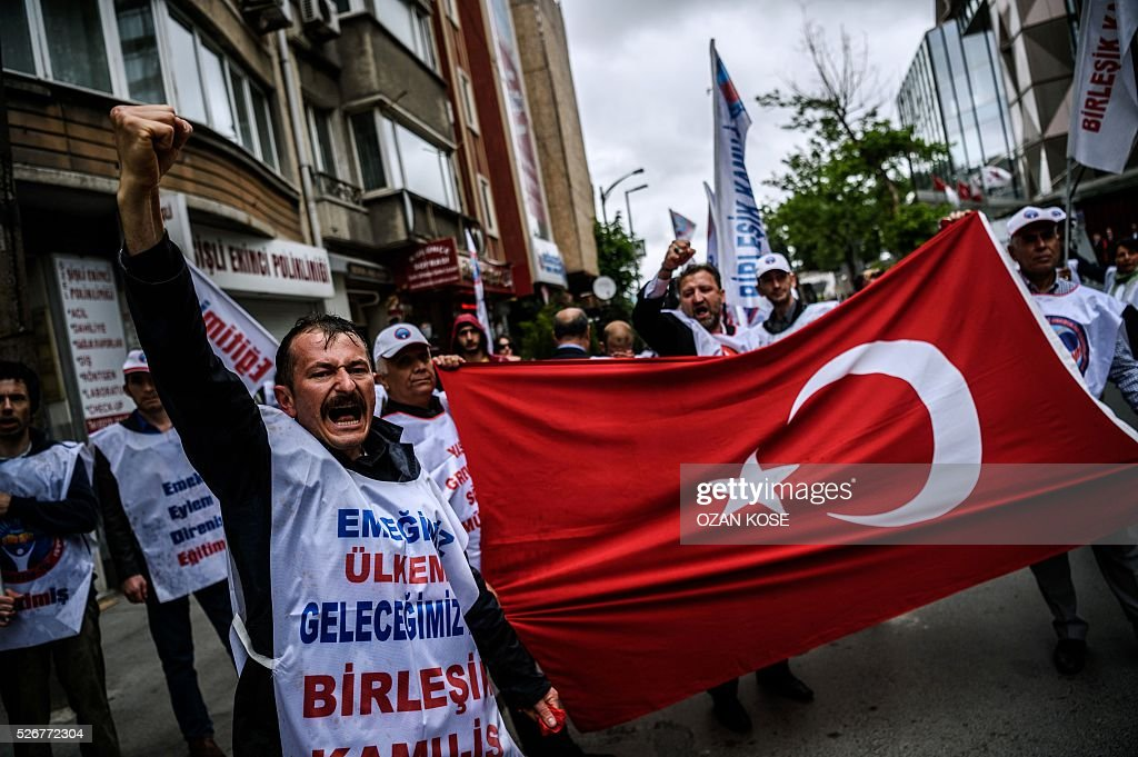 Demonstrators hold a Turkish flag and shout slogans during a May Day rally in Sisli, a district of Istanbul, on May 1, 2016. Turkish labour activists and leftists marked the annual May Day holiday, with thousands of security deployed and bracing for trouble after the authorities refused to allow protests in central Taksim Square. / AFP / OZAN