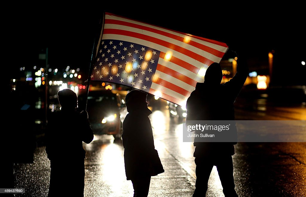 Demonstrators hold an upside down American flag as they stand in the street while protesting the shooting death of 18-year-old Michael Brown on November 22, 2014 in Ferguson, Missouri. Tensions in Ferguson remain high as a grand jury is expected to decide soon if Ferguson police officer Darren Wilson should be charged in the shooting death of Michael Brown.