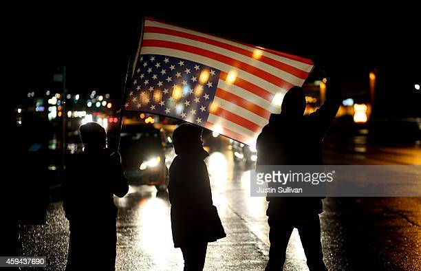 Demonstrators hold an upside down American flag as they stand in the street while protesting the shooting death of 18yearold Michael Brown on...