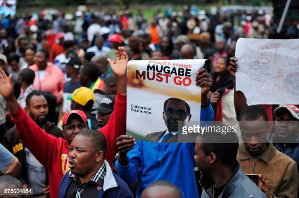 Demonstrators hold antiMugabe placards and shout slogans during a protest march demanding the resignation of Zimbabwe's president on November 18 2017...