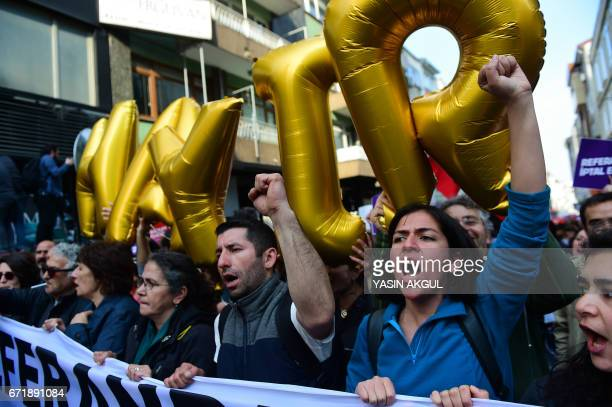 Demonstrators hold balloons reading 'No' and placards reading 'Referendum should be cancelled' during a protest at the Kadikoy district in Istanbul...