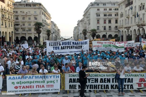 Demonstrators hold banners and placards during a protest against the government's austerity measures and reforms outside the annual Thessaloniki...