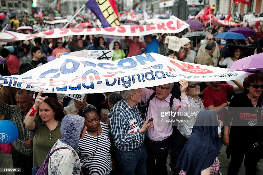 Demonstrators hold banners as they protest against the Government's austerity measures applied due to the Spanish economic crisis that began in 2008, at Puerta del Sol, Madrid, Spain on May 28, 2016.