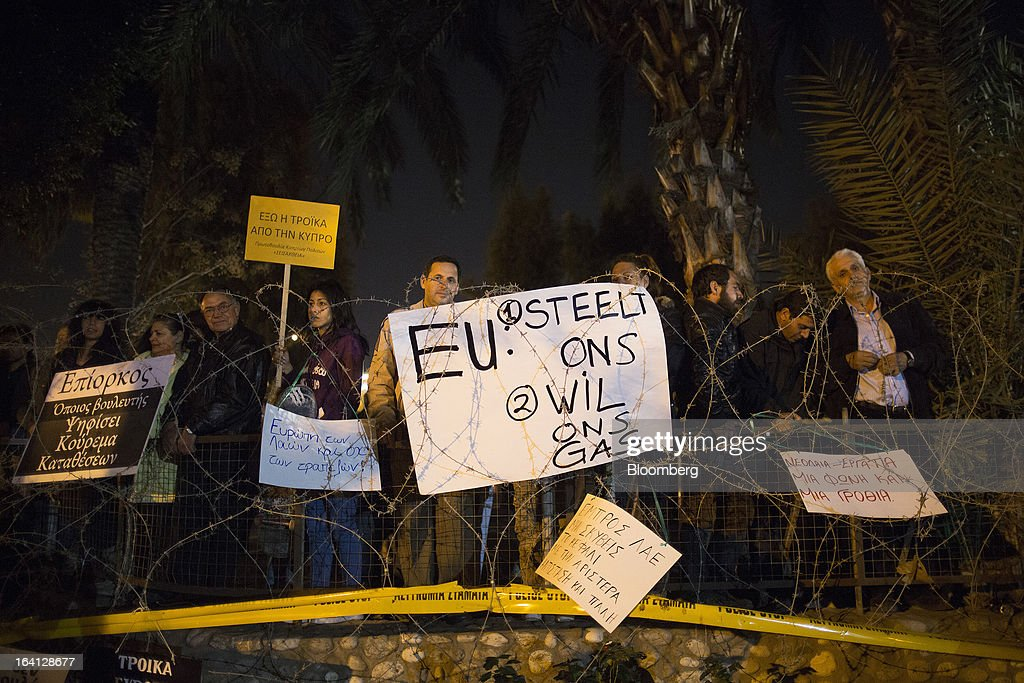 Demonstrators hold banners behind a razor security wire near the parliament during a protest against bank deposit tax plans in Nicosia, Cyprus, on Tuesday, March 19, 2013. Euro-area finance ministers told Cyprus to raise 5.8 billion euros ($7.5 billion) from bank depositors to unlock emergency loans, maintaining the revenue target while suggesting sparing small-scale savers. Photographer: Simon Dawson/Bloomberg via Getty Images