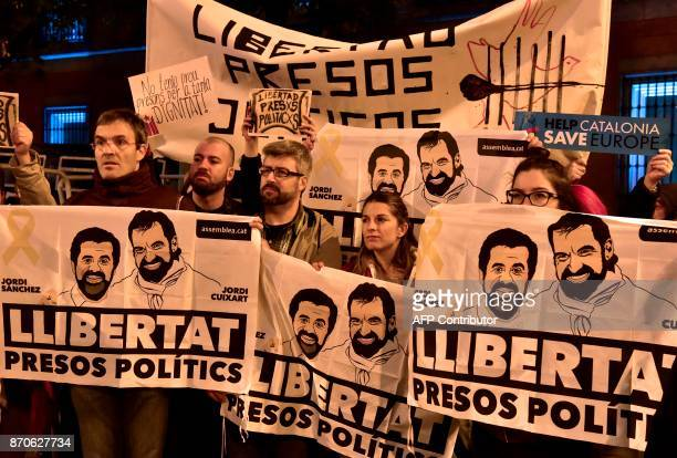 Demonstrators hold banners demanding 'Freedom for political prisoners' with pictures of detained leaders of Catalan separatist groups Jordi Cuixart...