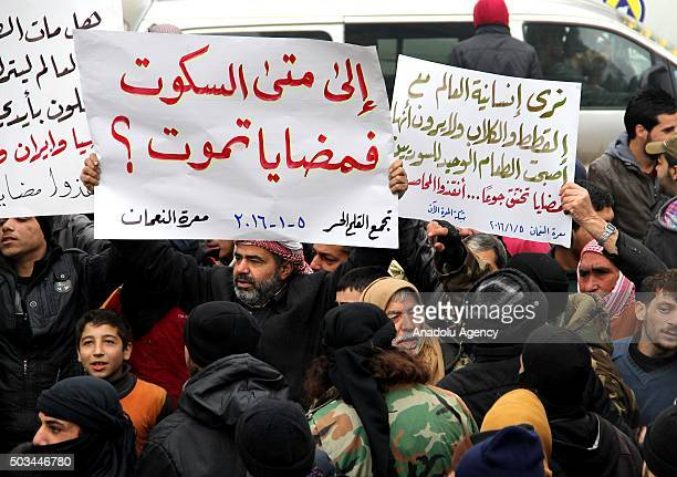 Demonstrators hold banners during a protest for civilians who starved to death in Madaya on January 5 2016 at Maret el Numan district of Idlib Syria